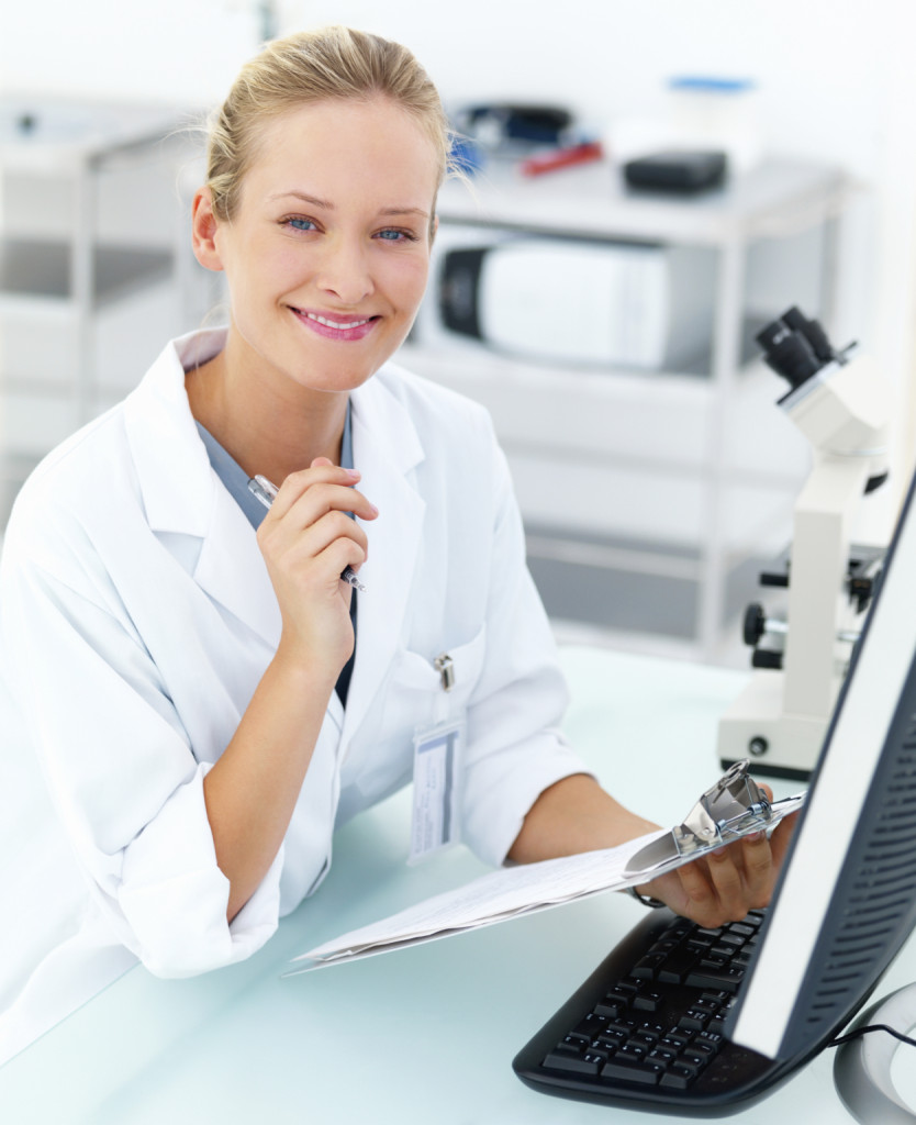 Smiling female researcher sitting at a laboratory and writing no